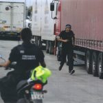 A man runs past lorries